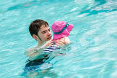 Swimming. Family with cute baby girl faving fun in outdoor swimming pool on hot summer day Royalty Free Stock Photo
