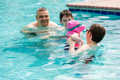 Swimming. Family with cute baby girl faving fun in outdoor swimming pool on hot summer day Royalty Free Stock Image
