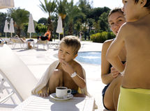 After swimming family near pool. Having hot tea Royalty Free Stock Photos