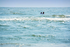 Swimming far. Mother and child swimming far away from shore royalty free stock images