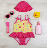 Swimming fashion set for girl. Swimming summer fashion set for cute little girl on wooden background, top view Stock Photo