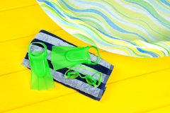 Swimming flippers. Swim flippers and eye goggles on a beach towel next to a plastic youth swimming pool Royalty Free Stock Images