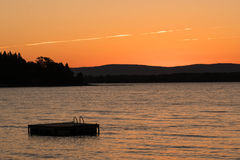 Swimming float and lake in Vermont at sunset. A swimming float on Lake Champlain at sunset with a view of the Appalachian mountains of Vermont in the background Stock Photography