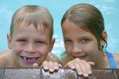 Swimming Fun. 2 siblings in pool Royalty Free Stock Image