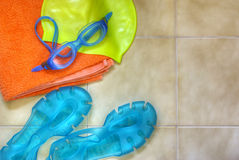 Swimming gear. Colorful swimming equipment over tiled swimming-pool floor Royalty Free Stock Images