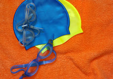 Swimming gear. Colorful swimming equipment over a orange towel texture Royalty Free Stock Image
