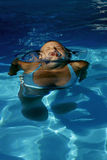 Swimming girl. Young beautiful woman swimming in a pool Royalty Free Stock Photography
