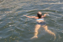 Swimming girl. Girl swimming in the harbour of Brouwershaven stock image