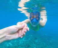 Swimming girl holds hand of partner. Romantic underwater photo. Snorkeling woman in full-face snorkeling mask. Swimming girl holds hand of partner. Romantic Royalty Free Stock Photography