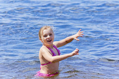 Swimming girl in pink swimsuit Stock Images