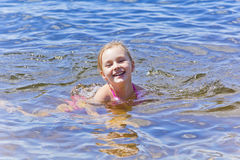 Swimming girl in pink swimsuit royalty free stock photography
