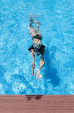 Swimming Girl. Vertical photo of a girl swimming in a vivid blue pool. She is diving with visible bubbles. She is at the end of a swimming race. Poolside is Stock Images