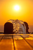Swimming girls silhouettes and splashing water against sea at sunset stock image