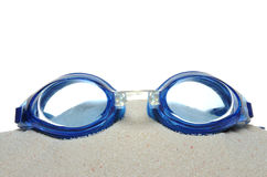 Swimming goggles. On the sand isolated on white background royalty free stock photos