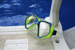 Swimming goggles. Laying beside a swimming pool stock photo