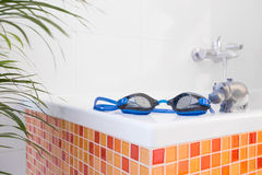 Swimming goggles on the bathtub Stock Photo