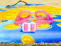 Swimming goggles on a colourful lilo Stock Image