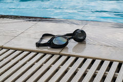 Swimming goggles on the edge of the pool Stock Image