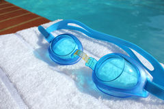 Swimming goggles at the edge of a swimming pool Stock Photo