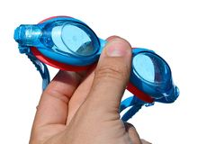 Swimming goggles held in small boy left hand on white background, with drops and traces of salt water on it Stock Image
