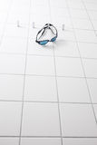Swimming goggles on white tile wall Royalty Free Stock Images
