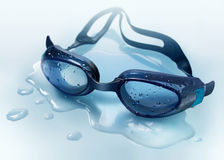 Swimming googles. Lying in a puddle Stock Photo
