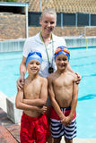 Swimming instructor with boys at poolside Royalty Free Stock Photography
