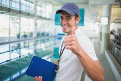 Swimming instructor smiling at camera by the pool Stock Photos