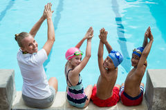 Swimming instructor with students at pool side Stock Photo