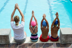 Swimming instructor teaching children at pool side Royalty Free Stock Images