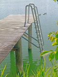 Dock by a lake in Austria. Wood dock in a sunny lake in Austria surrounded by vegetation Stock Photo