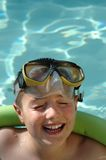 Swimming and laughing. Laughing kid in the pool; plenty of copy space included Stock Photos