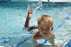 Swimming Lesson. Toddler Learning to Kick Feet in the Pool Stock Photos