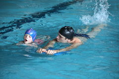 Swimming lesson - child practicing flutter kick with kick board with instructor. Close up of swimming lesson - child practicing flutter kick with kick board with royalty free stock image