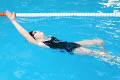 Swimming lessons for children in the pool - beautiful fair-skinned girl swims in the water.  stock photo
