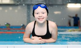 Free Swimming Lessons For Children In The Pool - Portrait Of A Beautiful White-skinned Girl In A Bathing Suit And Swim Cap Stock Photos - 128253143