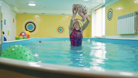 Swimming lessons for infant in the paddling pool. Cute little boy swimming with instructor in the pool and doing water exercises. Slow motion. Healthy family stock footage