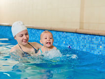 Swimming little baby with mother Stock Images