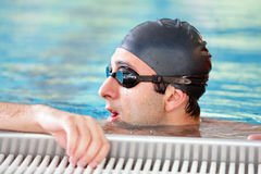 Swimming - male swimmer resting. Caucasian man doing breast swimming in pool wearing swimming cap and swim goggles Stock Photography