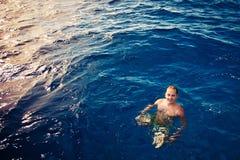 Swimming man in deep blue sea Stock Photos