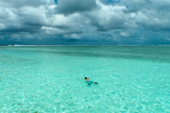 Man swimming in paradise. A man snorkeling in the maldives, on the meeru island resort, with dark blue clouds overhead and a wonderful ocean below Stock Image