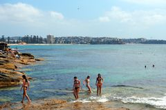 Swimming at Manly, Sydney, Australia. Swimming off rocks at Manly, a beachside suburb in Sydney, Australia, with city buildings and Manly Beach in background Stock Photo