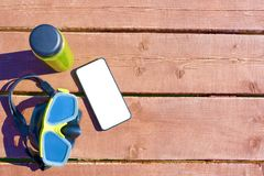 Swimming mask, bottle of smoothie and smartphone. With isolated screen on wooden table on sunny day on vacation. Copy space for text stock photography