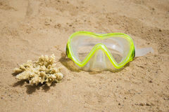 Swimming mask and a piece of yellow coral on a sandy beach. Sport and diving concept Stock Image