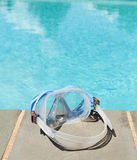 Swimming mask by side of blue pool Stock Image