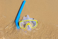 The swimming mask and snorkel to breathe under water, lie on the sand at the waters edge Stock Photography