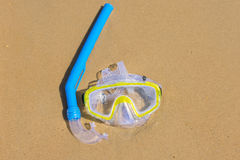 The swimming mask and snorkel to breathe under water, lie on the wet sand at the sea coast Royalty Free Stock Images