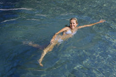 Swimming In The Mediterranean. A beautiful blond woman in a white bikini swims in the crystal clear blue Mediterranean Sea Royalty Free Stock Image