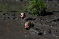 Swimming in the mud. Two muddy girls swim in a river of mud, as they participates in the 2013 marathon called a Mudathlon, in northwest Indiana Stock Image