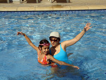 Swimming Partners. Young girl and her aunt mimicking synchronised swimming in the pool Stock Image